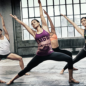 Women doing warrior yoga pose group fitness class