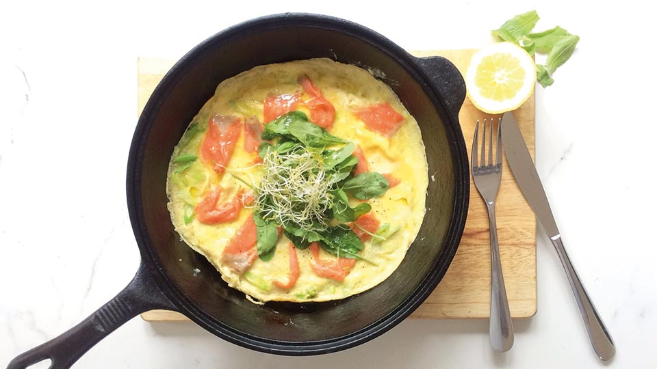 smoked salmon omlette in skillet on wooden block