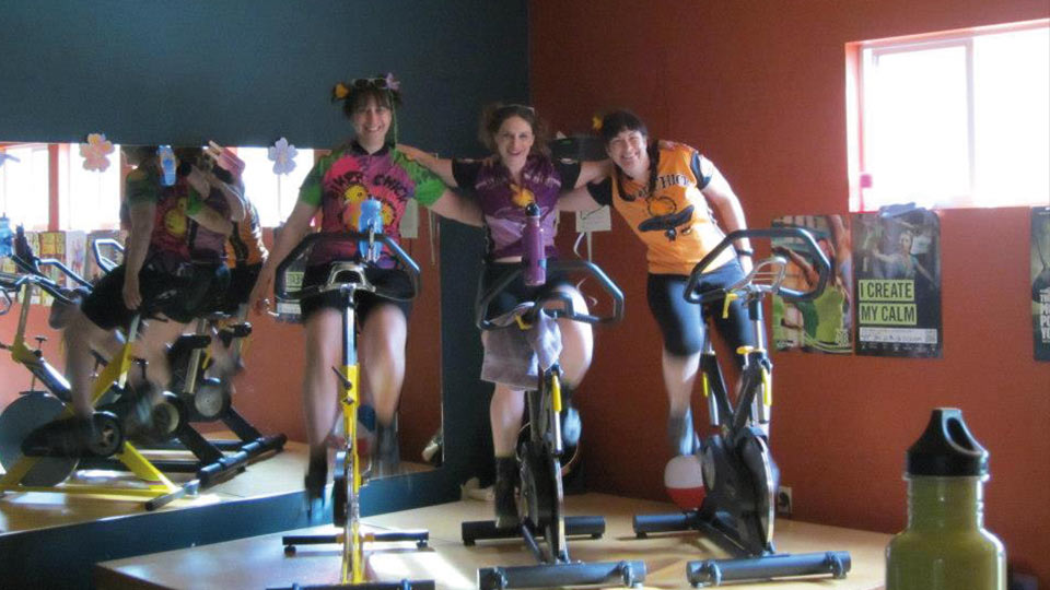 Three people doing an indoor cycling workout