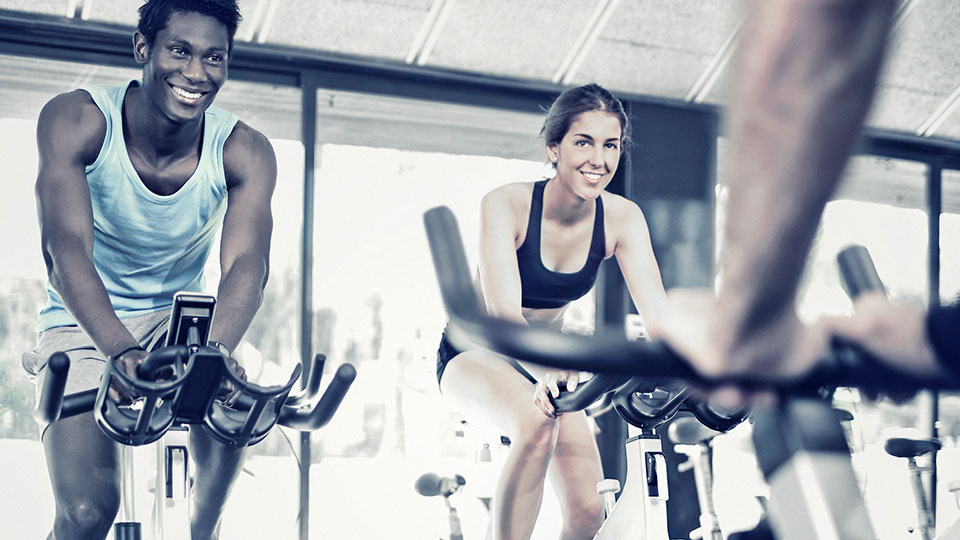 Two people doing an indoor cycling fitness class