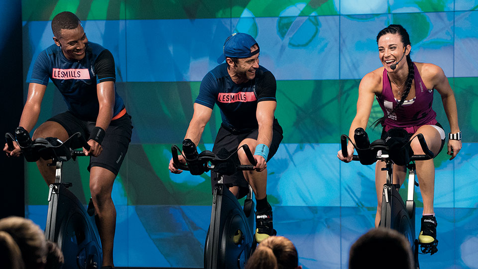 Three fitness instructors indoor cycling