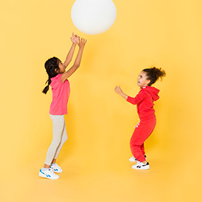 2 children bouncing ball with coordination